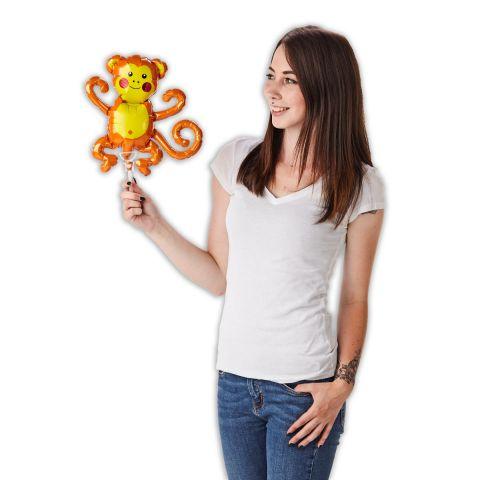 """Folienballon """"Äffchen"""" in braun/gelb auf Stab. Wird gehalten von einer Person."""