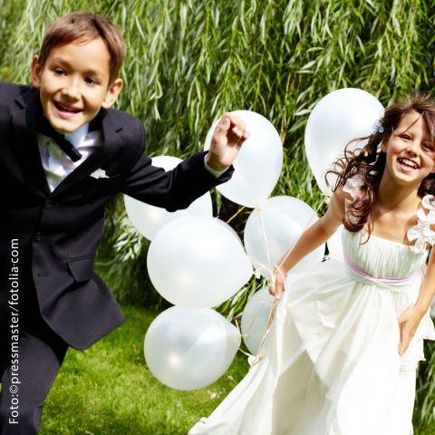 Kinder, Mädchen und Junge, festlich gekleidet laufen mit weißen Luftballons über eine Wiese