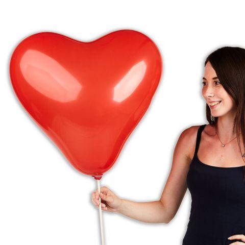 Großer, roter Herzballon im Größenverhältnis  zu einer Person zu sehen.