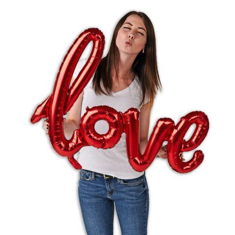 """Folienballongirlande, Schriftzug """"love"""" in rot. Zu sehen im Größenverhältnis zu einer Person, die den Schriftzug hält und einen Kussmund macht."""