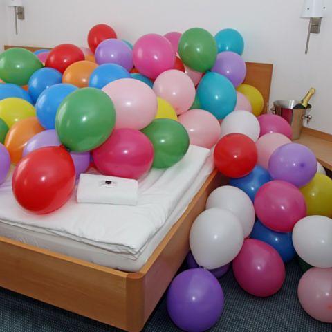 Viele bunte Luftballons, verteilt auf einem Bett oder im Schlafzimmer.