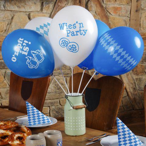 Oktoberfest-Deko-Luftballonns mit Haltestäben in einer Kanne auf einm Tisch, geschmückt für's Oktoberfest.