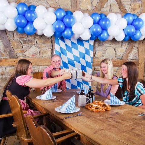 Oktoberfest-Girlande in blau weiß in Wirtshausszene mit 5 Personen am Tisch mit Bierkrug