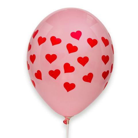 Rosa Luftballon mit vielen aufgedruckten roten Herzchen, rundum.