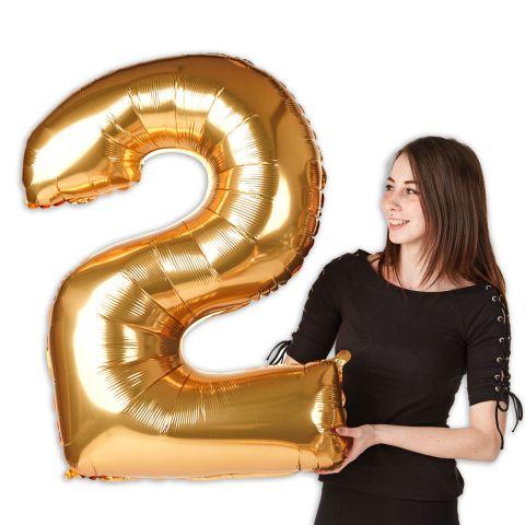 """Großer goldener Folienballon Zahl """"2"""" im Größenverhältnis zu einer Person zu sehen."""