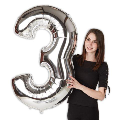 """Großer Folienballon Zahl """"3"""" im Größenverhältnis zu Person zu sehen."""