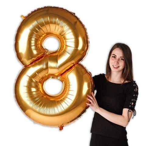 """Goldener Folienballon in Form von Zahl """"8"""" im Verhältnis zu einer Person zu sehen."""